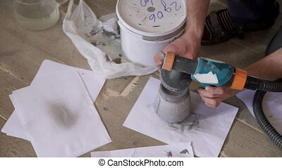 Painter on the wooden floor runs a small bottle for the gun.
