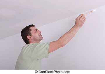 Painter painting a ceiling corner