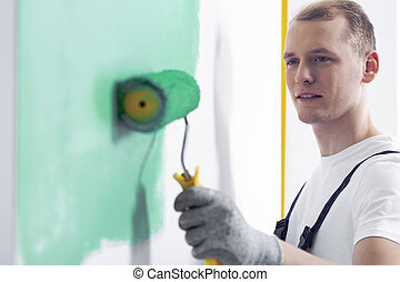 Painter painting a wall for a green color with a roller