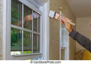 Painter painting the a window trim or molding of a house
