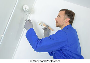 painter painting the wall with rollers