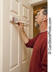 Painter painting trim around doors & windows