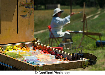 An outdoor oil painting class. The focus is on the palette.
