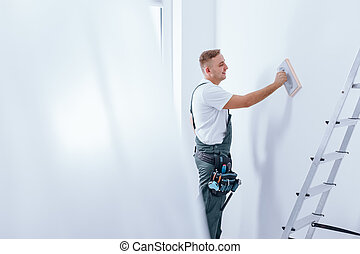 Painter smoothing the wall