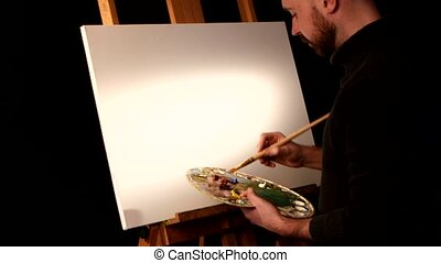 Painter starting drawing a new painting with oil paints holding the palette in his hand on easel, black background, back light