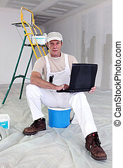 Painter taking a break to use his laptop