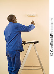 Painter using a Paint Roller - African American Construction...