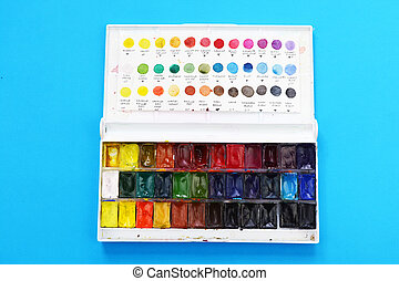 Watercolor paint in a box on blue background
