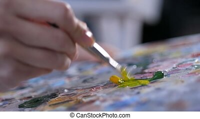 Painter with brush mixing acrylic paint on palette - Closeup...