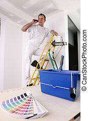 Painter with color swatch making telephone call