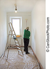 painter with paint roller in a white room