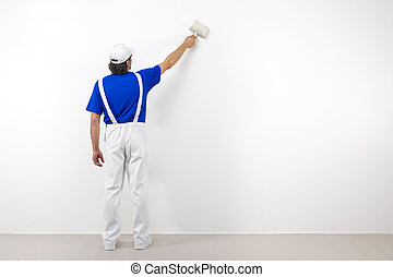 Painter with paintbrush on white wall