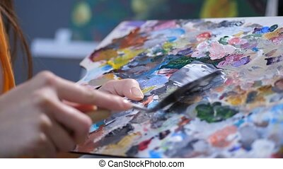 Painter with palette knife mixing acrylic paints - Close-up...