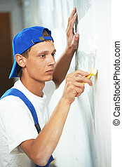 painter worker peeling off wallpaper from wall during...