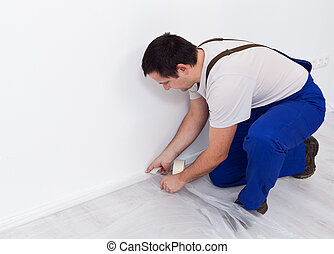 Painter worker preparing the room - laying protection film ...