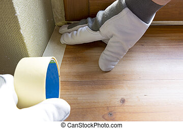 Painter worker protecting window sills with masking tape before painting at home improvement work
