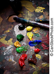 Painter\'s brushes and old pallet with multiple vibrant colors