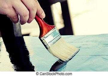 Paintimg furniture - Carpenter is painting wooden furniture...
