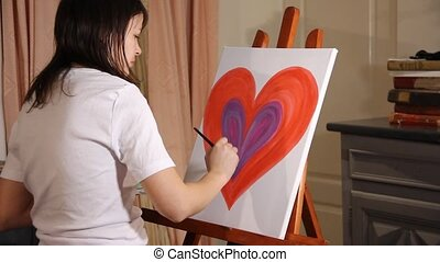 painting a big red heart - woman artist painting with...