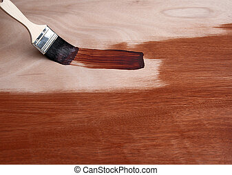 Painting a wooden surface with a brush - Painting a wooden...