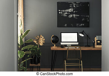 Painting above desk with computer desktop and lamp in grey and gold workspace interior. Real photo