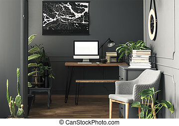 Painting above desk with mockup of computer desktop in grey workspace interior with armchair. Real photo