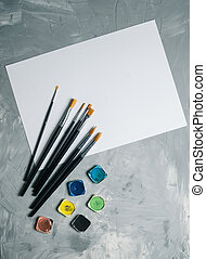 Painting brusches, white paper and watercolors on gray concrete background