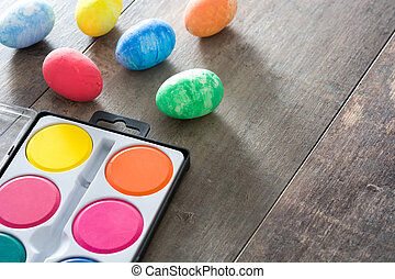 Painting Colorful Easter eggs on wooden background