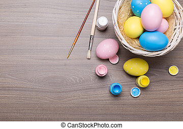 painting Easter eggs on wooden background
