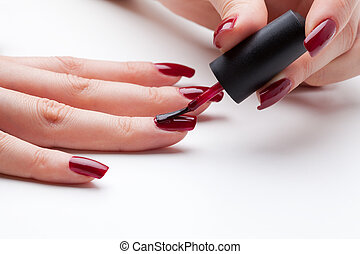 Painting fingernail with red enamel close-up