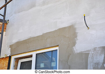 Painting house wall after plastering and stucco. Window insulation. Unfinished painting on house wall