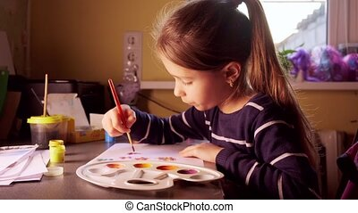 Painting paints at home. Girl paints beautiful flowers
