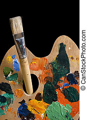 used painting palette and brush isolated on black