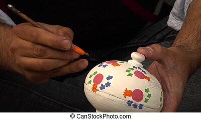 Painting paper mache powder box - A close up of a man...