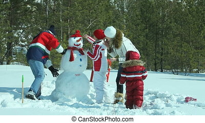 Painting snowman - Happy family of four painting the snowman...