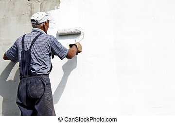 painting the facade - builder worker painting facade of...