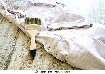 Painting Tools and outfit for home renovation on a wooden table.