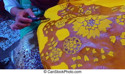 Painting water color on the fabric to make batik in...