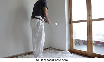 Painting white wall - Senior man painting a white wall, with...