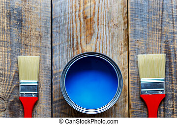 painting with can blue paint on wooden background