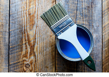 painting with can blue paint on wooden background top view