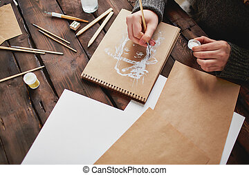 Image of young man hands drawing human with white gouache