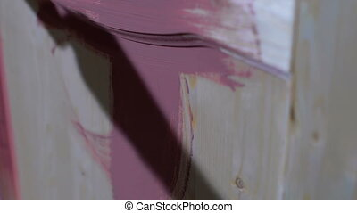 painting wooden door in purple color by brush. In the garage