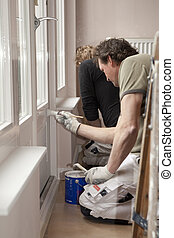 Painting wooden door in room - Housepainters at work in room...