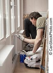 Painting wooden door in room - Housepainters at work in room...