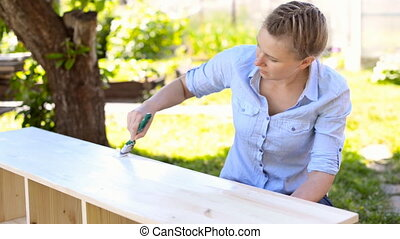Painting wooden furniture. - Woman with brush painting...