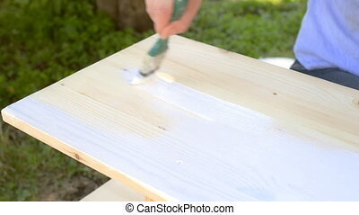 Painting wooden furniture. - Female hand with brush painting...