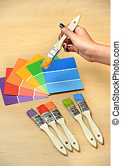 Paintrushes and Swatches with Hand Holding Brush