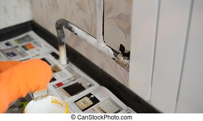 paints a heating radiator in  apartment