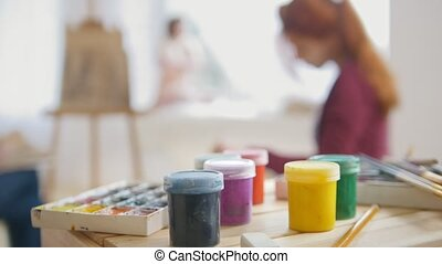 Paints and art supplies in front of artists performing...